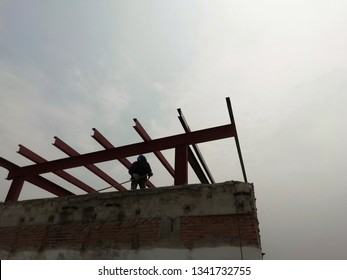 Silhouette of worker welding roof structure