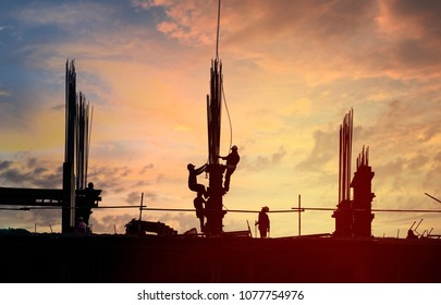 Silhouette of workers at building construction site in warm orange-blue twilight
