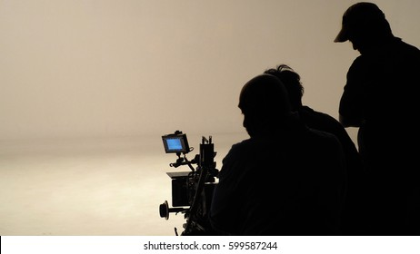 Silhouette of working people or production film crew are making movie or shooting tv on-line content live show in studio with camera equipment set.