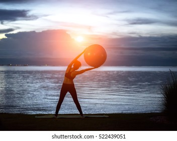 Silhouette yoga ball fit young woman in the beach sunset background.  Healthy Concept