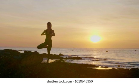 Silhouette yoga practice at sunset. Yong woman doing yoga exercise on the beautiful beach.