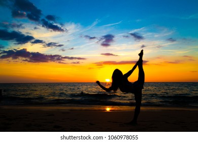 Silhouette yoga sign of healthy women on beach sunset colorful sky