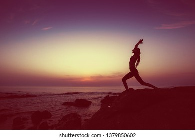 Silhouette of yoga woman doing exercises on the ocean beach in amazing twilight.