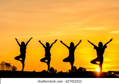 silhouette yoga for woman, group of young woman yoga during sunset with yellow sky, relaxing and happy feeling