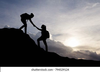 Silhouette of yong woman helping each other hike up a mountain at sunrise background. Business, teamwork, success and help concept. Vintage filter.