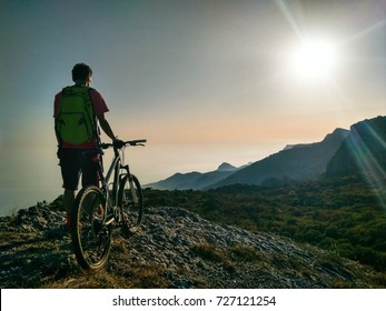 Silhouette of young active man with bicycle standing and looking forward at mountains panoramic background