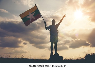 Silhouette of a young asian boy holding the Republic of the Union of Myanmar flag