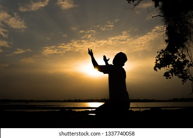 Silhouette Young asian muslim man praying on sunset,Ramadan festival concept