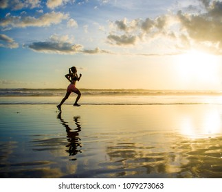 silhouette of young Asian sport runner woman in running workout training at sunset beach with orange sunlight reflection on the sea water in healthy lifestyle and wellness activity concept