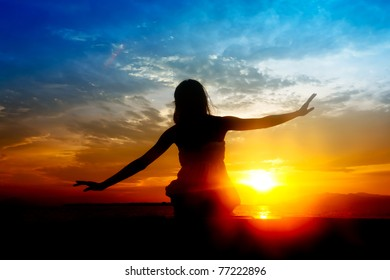 Silhouette of young Asian woman during colorful sunset