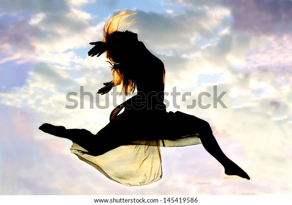 A silhouette of a young, attractive, dancing woman jumps through the air, with a beautiful cloudy sunset in the background outside.