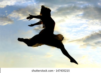 A silhouette of a young attractive woman dancing and jumping through the air in front of a beautiful cloudy sky