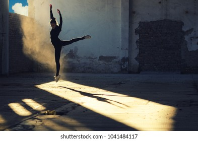 Silhouette of young ballerina jumping and dancing in abandoned building on sunny summer day.