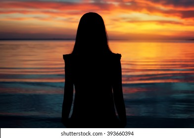 silhouette of young beautiful girl on sunset tropical beach. natural summer background