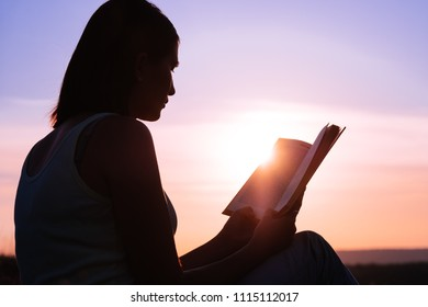 silhouette of a young beautiful woman at dawn sitting on the ground and carefully staring at the open book
