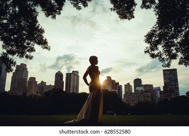 Silhouette of a young and beautiful woman, in elegant wedding dress, walking through Central Park, New York at sunset