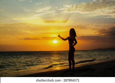 Silhouette of young beautiful woman on the beach at sunset sky