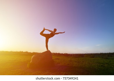 Silhouette of young blonde girl in sport suit practice yoga on a picturesque green hill in the evening at sunset. The concept of exercising and healthy lifestyles