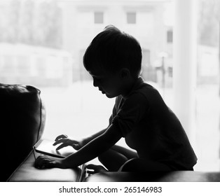 A silhouette of a young boy on a tablet or computer.   Symbolising the dangers of the internet.