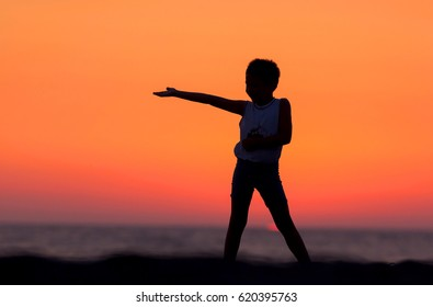 Silhouette of young boy playing on the beach