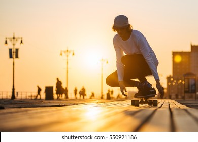 Silhouette of young boy riding longboard on the boardwalk, warm summer time sunset