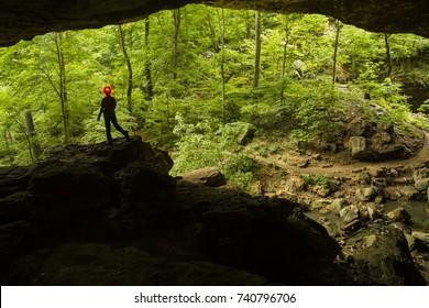 Silhouette of a young boy standing at the mouth of a cave with green forest in the background.