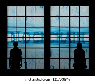 Silhouette of a young businessmen standing and looking through big window at blue blockchain cyberspace background.