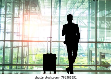 Silhouette of young businesspeople stand at the airport during sunset and are talking on the phone to inform them of their important business travel overseas.