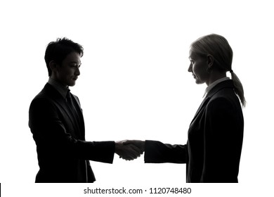 Silhouette of young businessperson shaking hands.