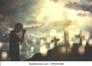 Silhouette of a young Christian man praying to god and folding palms with three crucifixes at sunrise