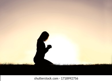 A silhouette of a young Christian woman kneeling in prayer on a summer day.