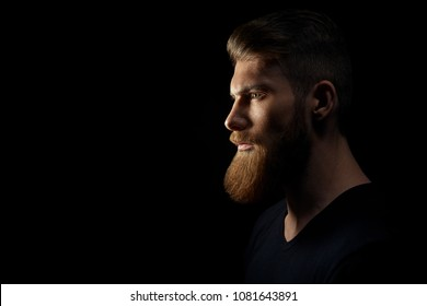 Silhouette of young confident handsome bearded man hipster wearing black knit hat. Studio shot on dark background Image with free copy space