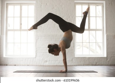 Silhouette of young cool attractive yogi woman practicing yoga concept, standing in Adho Mukha Vrksasana exercise, Downward facing Tree pose, working out, wearing sportswear bra and pants, full length