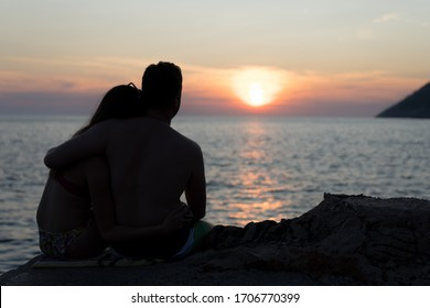 Silhouette of a young couple at the beaching watching the sunset