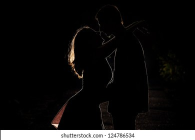 Silhouette of a young couple in the dark