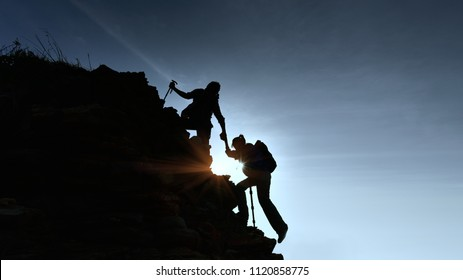 silhouette Young couple  hikers climbing up on the peak of mountain. Climbing ,Helps and Team work concept .