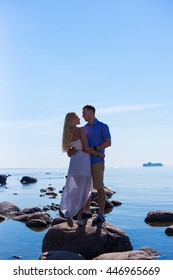 silhouette of young couple in love over beautiful sea background