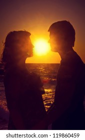 Silhouette of a young couple in love at sunset
