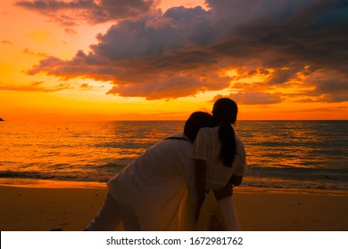 Silhouette of a young couple romantic  beautiful sunset on the beach, together is feel happiness.