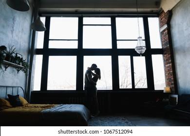 Silhouette von jungen Paaren, die volle Länge und Umarmung auf Fensterhintergrund im Inneren