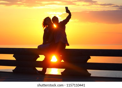 Silhouette young couple at sunset by the sea. Selfie