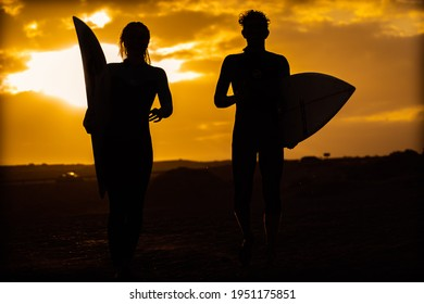Silhouette young couple surfers stay on the sunset beach. Surfers walking with surfboards to the beach. Extreme sport, travel and vacation concept.