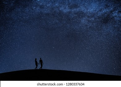 Silhouette of young couple under stars. The concept on the theme of love