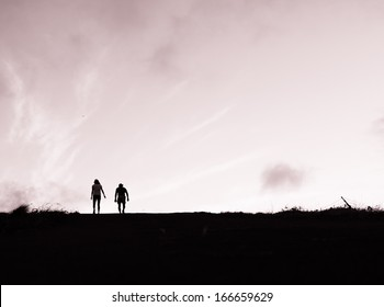 Silhouette of young couple walking side by side.