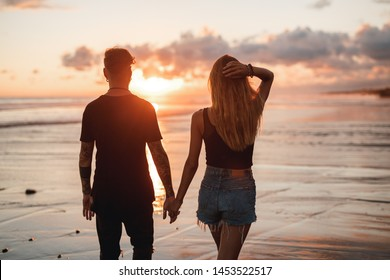 Silhouette of young couple walking at sunset on the beach .  Happy lovers holding hands at night by the ocean with big red sun background. Concept of love and tropical holidays with warm colors
