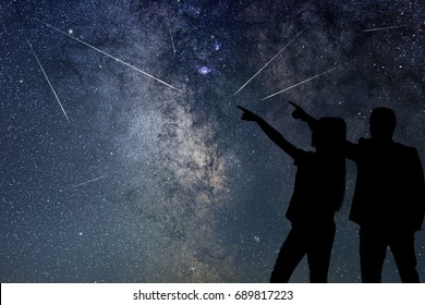 Silhouette of young couple watching Meteor Shower. Nigh Sky.