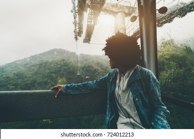 Silhouette of young curly black girl in jeans jacket sitting inside of cabin of mountain lift, smiling and looking aside on beautiful rainy hills of Rosa Khutor resort, Sochi, Russia