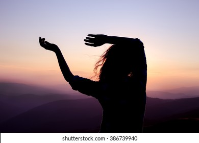 Silhouette of a young dancing woman with long wavy hair in the mountains in the backdrop of the setting sun