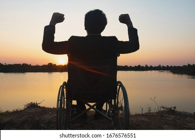 Silhouette young disabled man seeing river background.He is raise a hand to and sitting on wheelchair.Photo concept depression and Patient.