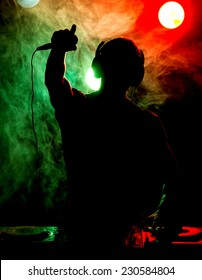 Silhouette of a young DJ at work with a microphone and the club lights on the background.